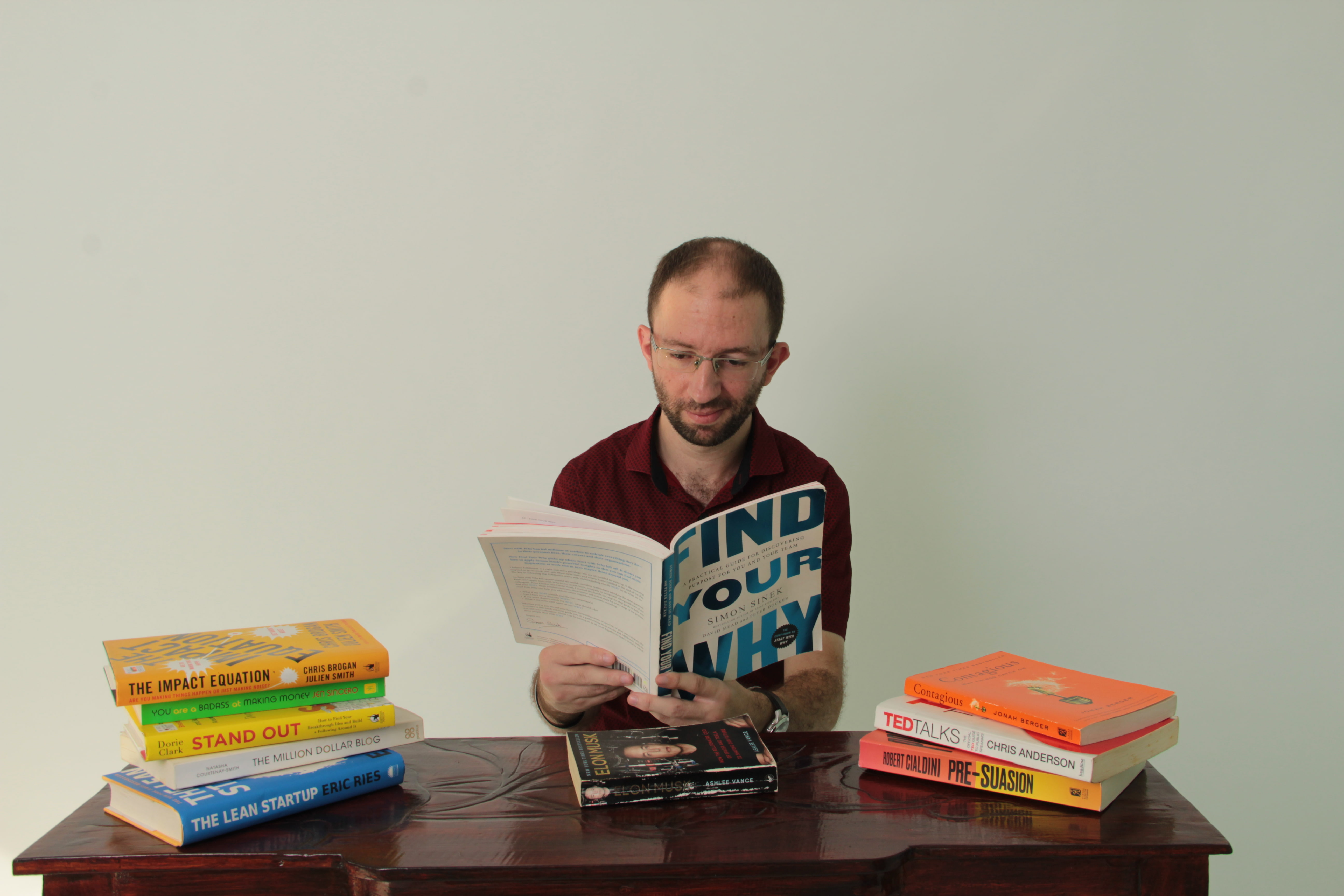 Person sitting at a desk full of business books, reading abut the WHY Discovery from the book 'Find Your Why'