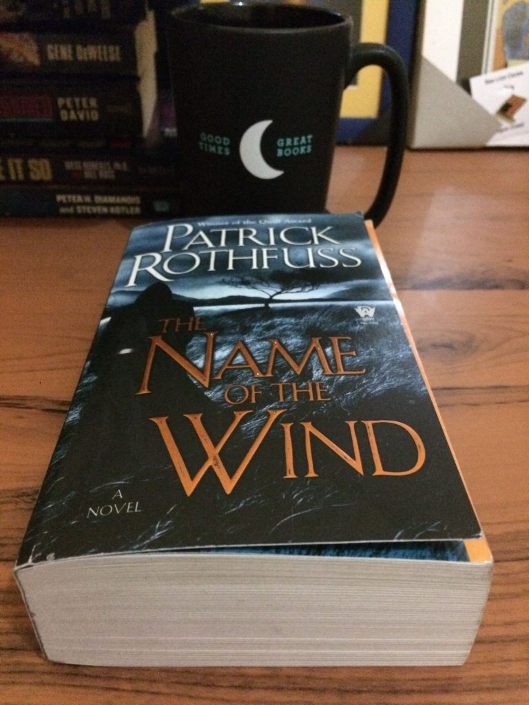 the book featuring kvothe, the name of the wind sitting on a wooden desk with a stack of books and coffee mug behind it