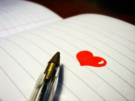 an open notebook with a pen on top and a red drawn heart as the content